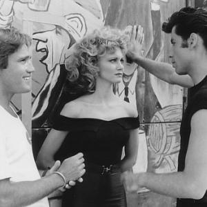 Director Randal Kleiser (left) with Olivia Newton-John (center) and John Travolta (right) on the graduation carnival set.