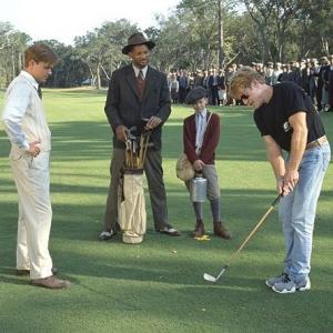 Director Robert Redford demonstrates a golf swing for his stars
