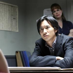 Roy Vongtama as Detective Lee in Death Clique (2014). Stephanie Erb as Detective Gaines (background).