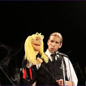 Still of Corey Tomicic and puppet Millie performing at the Candyass Cabaret