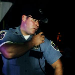 Officer Joseph Gates radioing in sighting of Jon Brewers character in Jakes Song